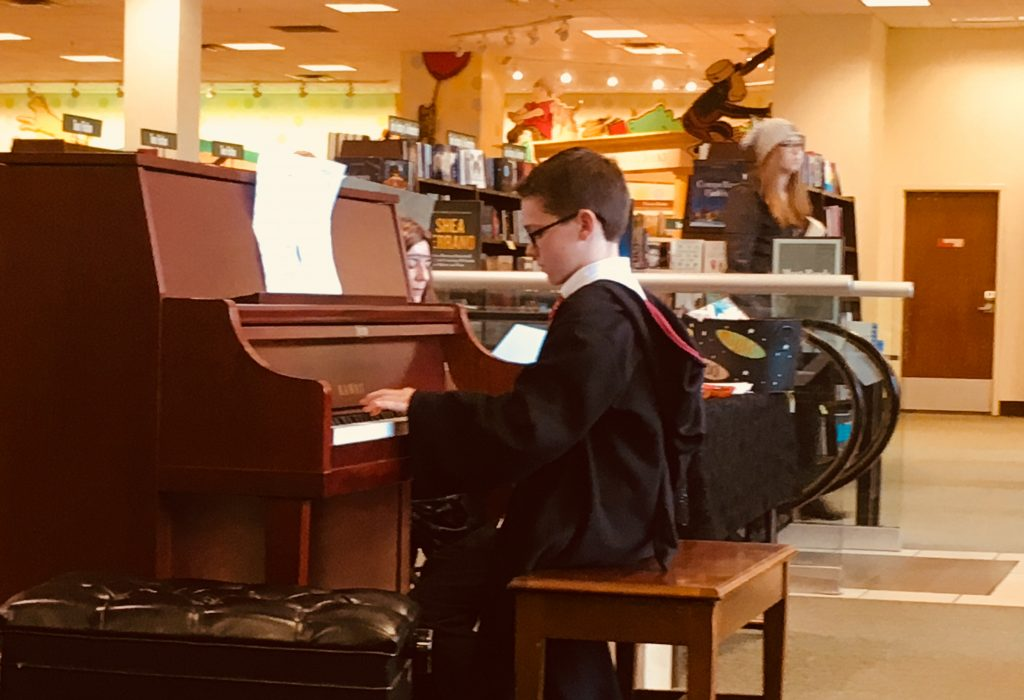 student dressed as Harry Potter plays piano at bookstore